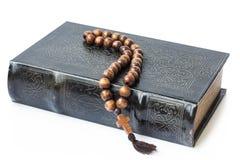 Rosary στη Βίβλο που απομονώνεται σε ένα άσπρο υπόβαθρο Στοκ φωτογραφία με δικαίωμα ελεύθερης χρήσης