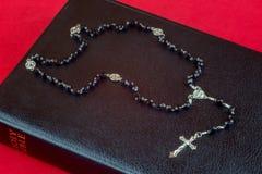 Rosary χάντρες και Crucifix στην κλειστή Βίβλο Στοκ Εικόνες