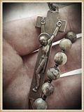 Rosary. Image of a male hand holding a single decade rosary and crucifix