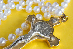 Rosary. Pearl beads and golden crucifix against a yellow background Stock Images