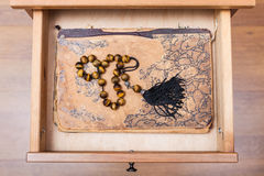 Rosary on ansient book in open drawer. Top view of rosary on ansient book in open drawer of nightstand royalty free stock image