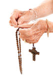 Rosary Beads. Closeup of senior woman's hands holding Catholic rosary beads. Isolated on white. * The traditional religious symbols on the crucifix aren't stock images