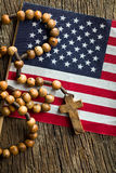 Rosary beads with american flag. Top view of rosary beads with american flag on wooden background royalty free stock photo