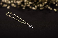 Rosary beads with blurred white small flowers, black background Stock Photography