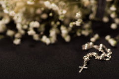 Rosary beads with blurred white small flowers, black background Royalty Free Stock Image