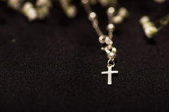 Rosary beads with blurred white small flowers, black background Stock Photo