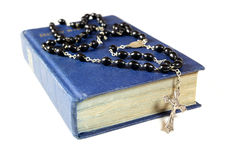 Rosary beads and Bible. Rosary beads and cross drapped over a bible Royalty Free Stock Image