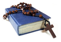 Rosary beads and Bible. Rosary beads and cross drapped over a bible Royalty Free Stock Images