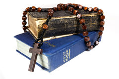 Rosary beads and Bibles. Rosary beads and cross drapped over two bibles Royalty Free Stock Photography