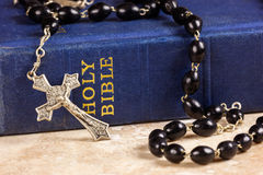 Rosary beads, cross and Bible. Rosary beads and cross lying on a bible Stock Photos