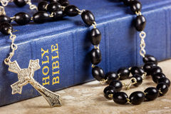 Rosary beads, cross and Bible. Rosary beads and cross lying on a bible Stock Image