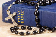 Rosary beads, cross and Bible. Rosary beads and cross lying on a bible Stock Images
