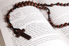 Rosary beads, cross and Bible. Rosary beads and cross lying on an open page of the bible Stock Photography