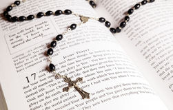 Rosary beads, cross and Bible. Rosary beads and cross lying on an open page of the bible Stock Images