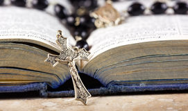 Rosary beads, cross and Bible. Rosary beads and cross lying on an open page of the bible Stock Image