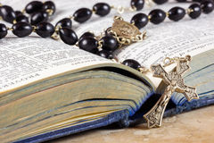 Rosary beads, cross and Bible. Rosary beads and cross lying on an open page of the bible Royalty Free Stock Photo