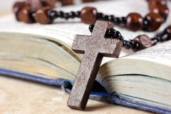 Rosary beads, cross and Bible. Rosary beads and cross lying on an open page of the bible Stock Photos