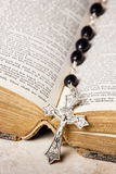 Rosary beads, cross and Bible. Rosary beads and cross lying on an open page of the bible Royalty Free Stock Photography