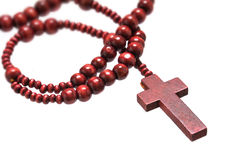 Rosary beads with cross made of red wood isolated on a white background, close up with selected focus on christ. Narrow depth of field stock photography