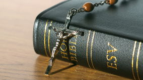 Rosary beads falling onto bible on a table stock video