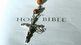 Rosary beads falling onto first page of bible stock footage