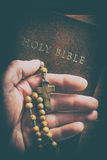 Rosary beads in hand. Rosary beads in hand and holy bible Royalty Free Stock Photography