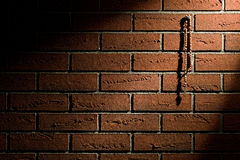 Rosary beads hanging on brick wall Stock Image
