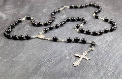 Rosary Beads. Rosary beads and metal cross  on a slate background Royalty Free Stock Image