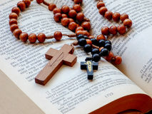 Rosary beads on opened holy Bible Stock Images