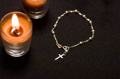 Rosary beads with an orange candle in black background, above view Royalty Free Stock Photos