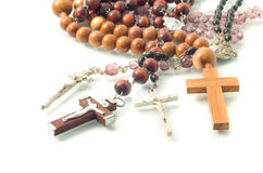 Rosary beads over white with focus on crosses Royalty Free Stock Photos
