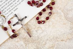 Rosary beads and psalms. Rosary beads on a book of psalms and sandstone background with copy space stock photo