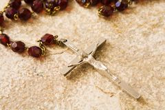Rosary beads on stone. Rosary beads on a sandstone background royalty free stock photos
