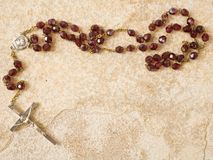 Rosary beads on stone with copy space. Rosary beads on a sandstone background with space for text Stock Photography
