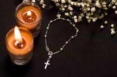Rosary beads with two blurred orange candles and small flowers, black background, above view Stock Photo