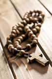 Rosary beads on wooden background Royalty Free Stock Photography