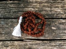 Rosary beads on the wooden background. Rudraksha Mala for Mantras. 108 beads. Rosary beads on the wooden background. Rudraksha Mala for Mantras royalty free stock photography
