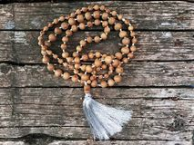 Rosary beads on the wooden background. Rudraksha Mala for Mantras. 108 beads. stock photos