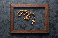 Rosary beads in wooden frame. The rosary beads in wooden frame royalty free stock image