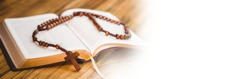 Rosary on bible and white transition Stock Photo