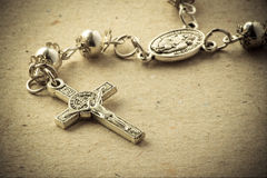 Rosary Crucifix. A rosary crucifix over a paper background Stock Photo
