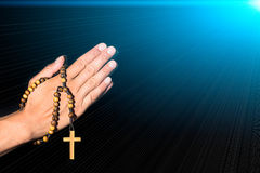 Rosary in hand on black background.  Stock Photos