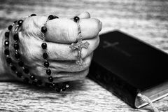 Rosary in hand and prayer book. Rosary in old hand and black prayer book. Black and white photography Royalty Free Stock Photos