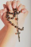 Rosary in hands. Brown rosary in praying hands Stock Images