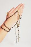 Rosary in hands. Hands holding a brown rosary Royalty Free Stock Image