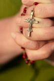 Rosary in hands Stock Image