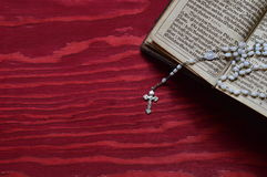Rosary with old ancient book on red wood Royalty Free Stock Image