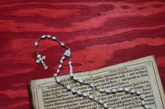 Rosary with old ancient book on red wood Royalty Free Stock Images
