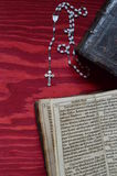 Rosary with old ancient book on red wood Stock Image