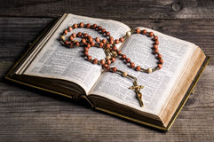 Rosary on old Bible. Rosary with cross on old open Bible Royalty Free Stock Photo